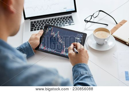 Touching Stock Market Graph On A Touch Screen Device. Trading On Stock Market Concept.
