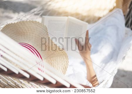 Young Lady Reading A Book In Hammock On Tropical Sandy Beach