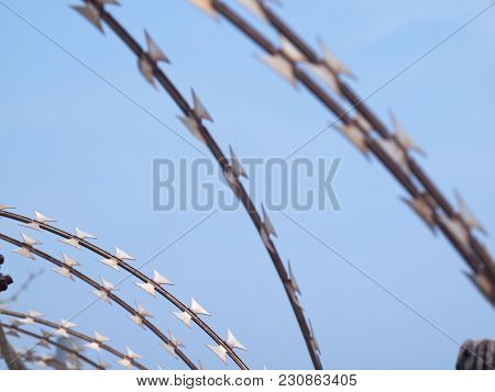Grunge Barbed Wire Fence Against Blue Sky