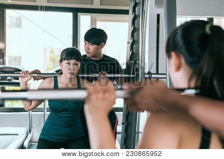 Woman Doing Squats With Her Personal Trainer