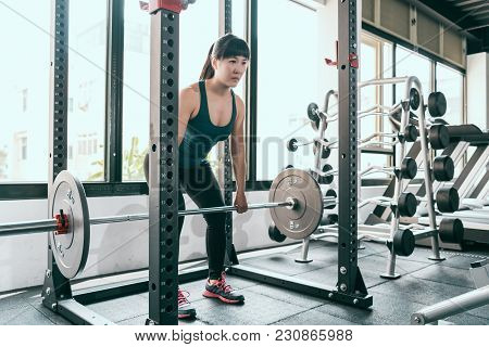 Fitness Woman Deadlift Barbell In Smith Machine