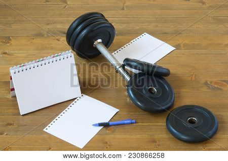 Sports Records On A Wooden Background, Next To The Fitness Equipment