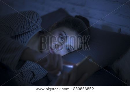 Portrait Of Young Beautiful Latin Woman Using Mobile Phone Late Night Sleepless Lying In Bed In The