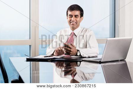 Indian Senior business executive sitting at desk in skyscraper office checking his smart phone