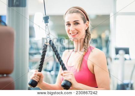 Portrait of a beautiful fit woman smiling and looking at camera, while exercising triceps pushdown at the rope cable machine for toned arms at the gym