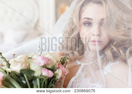 Tender Portrait Of A Beautiful Bride Under A Veil Holding Bouquet.