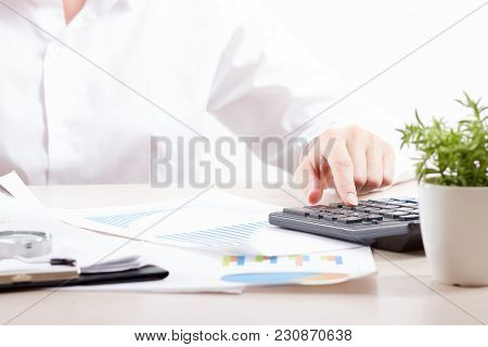 Close Up Of Female Accountant Or Banker Making Calculations. Savings, Finances And Economy Concept.