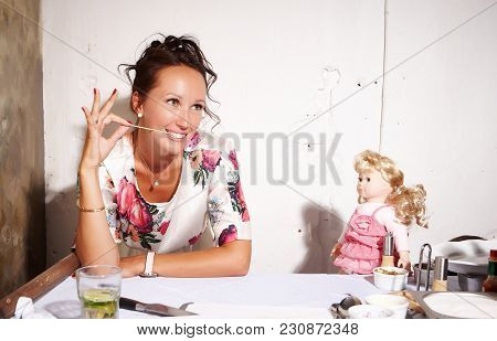 Brunette Woman In A Colorful Dress Sitting At The Table.