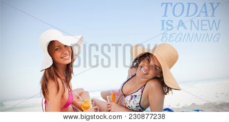 Today is a new beginning against young smiling women lying on beach towels while looking at the camera