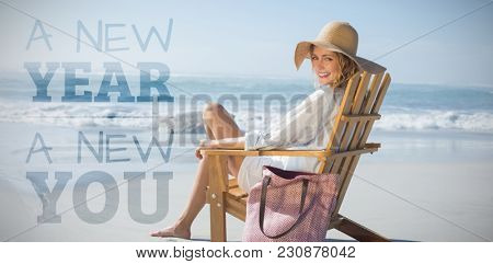 New year new you against smiling blonde sitting on wooden deck chair by the sea