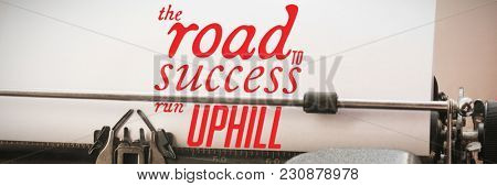 The road to success run uphill against close-up of typewriter