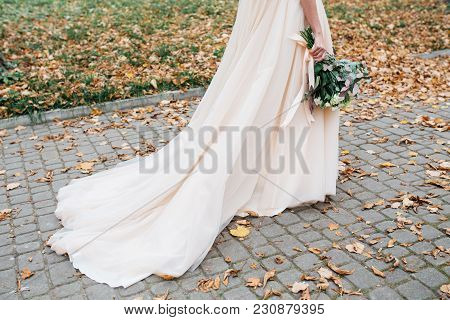 Beautiful Bride With A Wedding Bouquet In Their Hands Outdoors In A Park. Wedding Day
