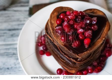 Chocolate Pancakes In The Shape Of Heart, Poured With Chocolate Icing And Red Frozen Cranberries On