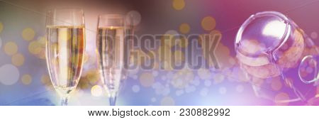 Champagne flutes on table against overhead of top of champagne bottle