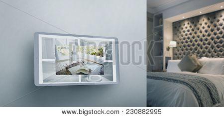 Screen of digital tablet against illuminated neat bedroom