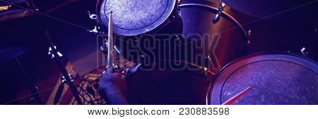 Cropped hands of drummer playing drum kit in nightclub