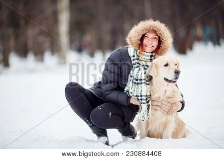 Picture Of Girl In Black Jacket Squatting Next To Dog In Winter Park During Day