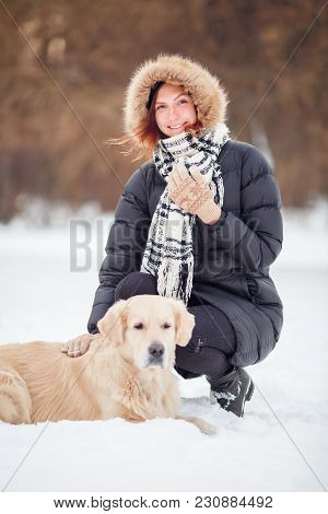 Photo Of Happy Woman In Scarf Sitting Next To Labrador At Winter Park In Afternoon