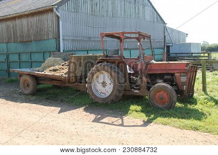 A Vintage Rusty Tractor On A Working Agricultural Farm.