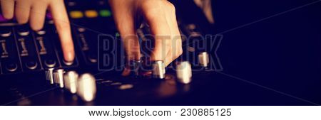 Cropped hands of audio engineer using sound recording equipment at recording studio