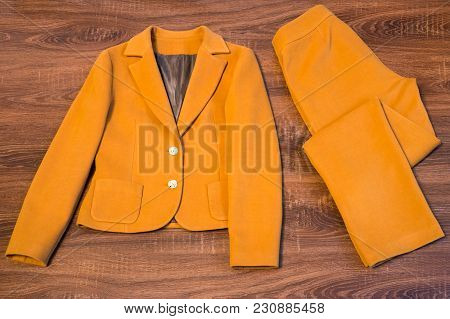 Stylish Female Blazer And Trousers On Wooden Background