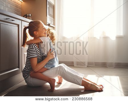 Family Mother And Child Daughter Hugging In Kitchen On Floor.
