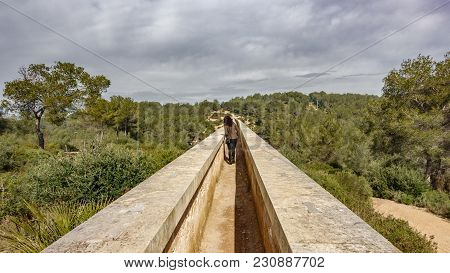 The Ferreres Aqueduct Top View With Tourist Walking