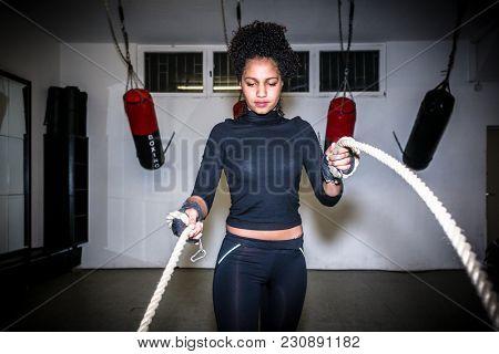 Young fit woman exercising with battle ropes during functional training indoors