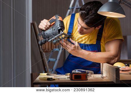 Worker working in repair workshop in woodworking concept