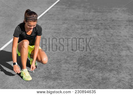 Sport girl getting reaady to start jogging on city street tying up laces of running shoes. Active urban lifestyle. Healthy woman outdoors.