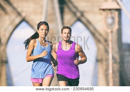 New York city runners running training for marathon on Brooklyn bridge NYC in urban cityscape. Fit young couple doing their workout routine on a summer day.