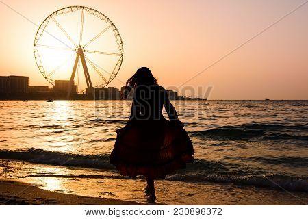 Girl On The Jbr Beach With Ain Dubai Ferris Wheel At Sunset