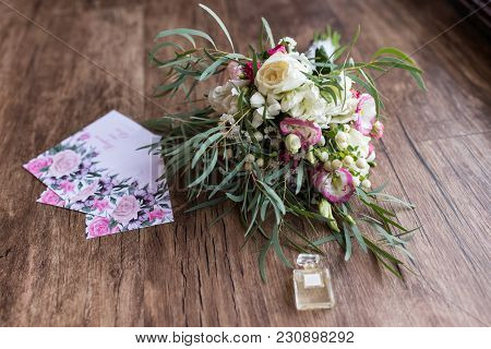 Lush Bridal Bouquet With White Roses And A Lot Of Greenery And A Few Invitations Lying On The Wooden