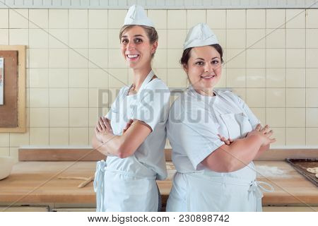Two baker women standing proud in their bakery with arms folded