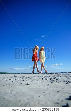 Women With Blonde Hair Outdoor. Twins In Summer Walk On Blue Sky Background. Girls With Sexy Legs, F