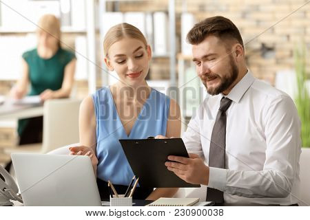 Male receptionist with trainee at workplace