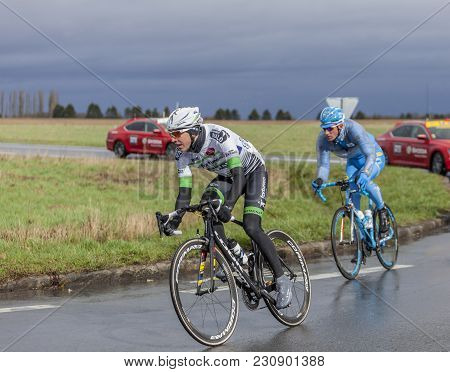 Cernay-la-ville, France - March 5, 2017: Two Cyclists, Romain Hardy And Gatis Smukulis Riding On A W