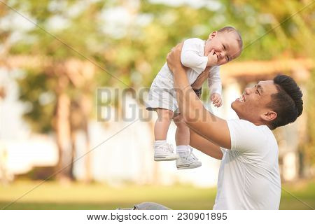 Happy Excited Father Playing With His Baby Boy Outdoors