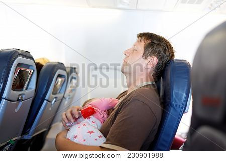 Young Tired Father And His Baby Daughter Sleeping During Flight On Airplane Going On Vacations. Dad