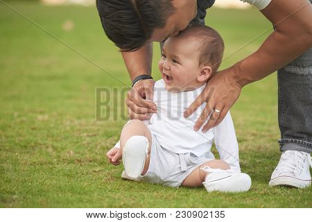 Father Bending To Kiss His Adorable Baby Boy On Forehead