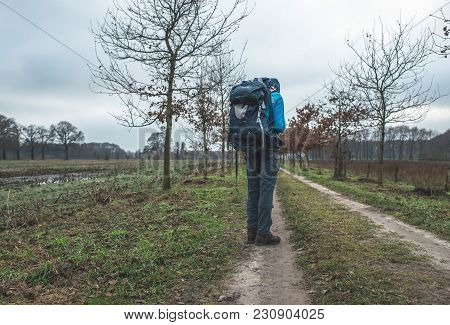 Hiker With Backpack Standing On Dirt Road With Tire Tracks.