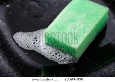 Wet Black Dish And Sponge With Detergent .