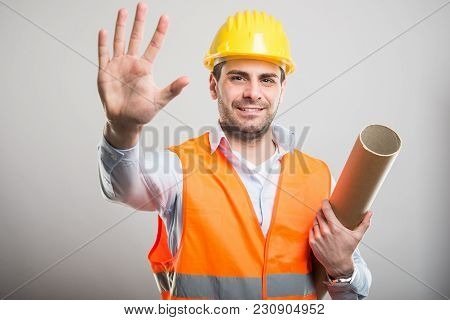 Portrait Of Young Architect Holding Blueprints Showing Number Five