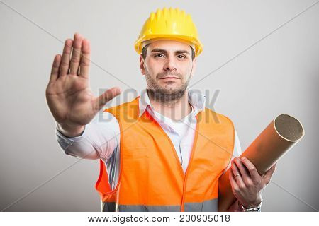 Portrait Of Young Architect Holding Blueprints Making Stop Gesture