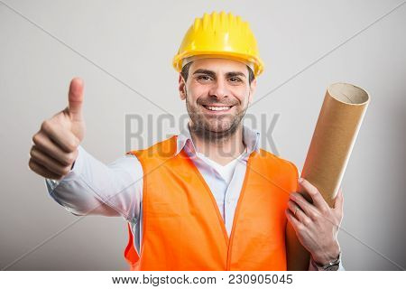 Portrait Of Young Architect Holding Blueprints Showing Thumb Up