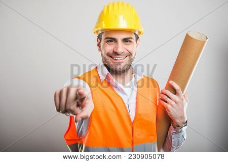 Portrait Of Young Architect Holding Blueprints Pointing Camera