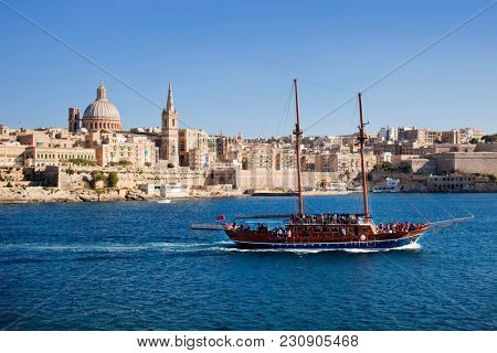 A boat passes the center of town in the Valletta harbor. Valletta, Malta - May, 2015