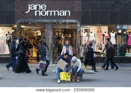 London, England - July 12, 2016 A Man Helps His Wife Pack Purchases Near Jane Norman