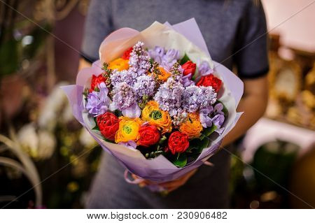 Woman Holding A Beautiful Bouquet Of Flowers Consisting Of Red Tulips, Lilac And Orange Ranunculus