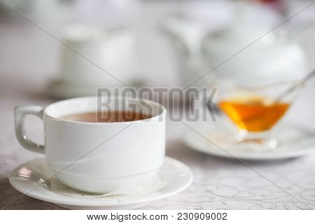 White Cup Of Tea With Honey On A White Background With Teapot. Serving Tea. Honey In Saucer.